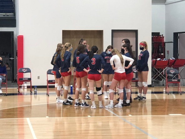 The NCLA girl's varsity volleyball team huddled during a game on their senior night